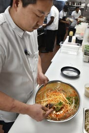 """Grant Vella, also known as """"Chef G"""" whips up a papaya and greens salad on May 2."""