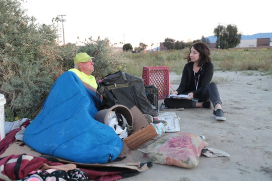 Health reporter Nicole Hayden speaks with and surveys a man experiencing homelessness in Indio, Calif. on March 14, 2019.