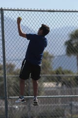 Giovanni Miranda climbs a fence to retrieve a tennis ball during his match against Aliso Niguel, Indio, Calif., May 1, 2019.