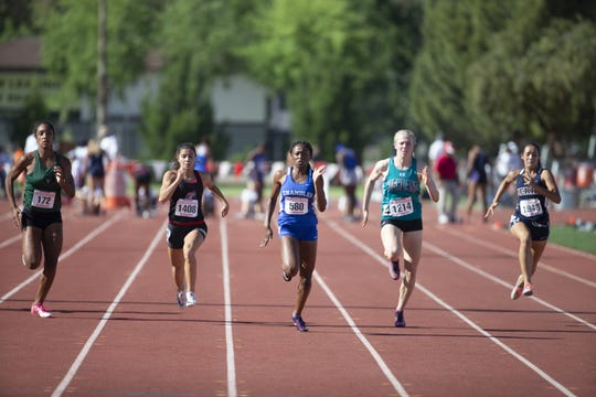 Chandler High's Trinity Henderson leads and wins the Div. I Girls 100 meter dash compete during the state track and field meet at Mesa Community college on May 1, 2019.
