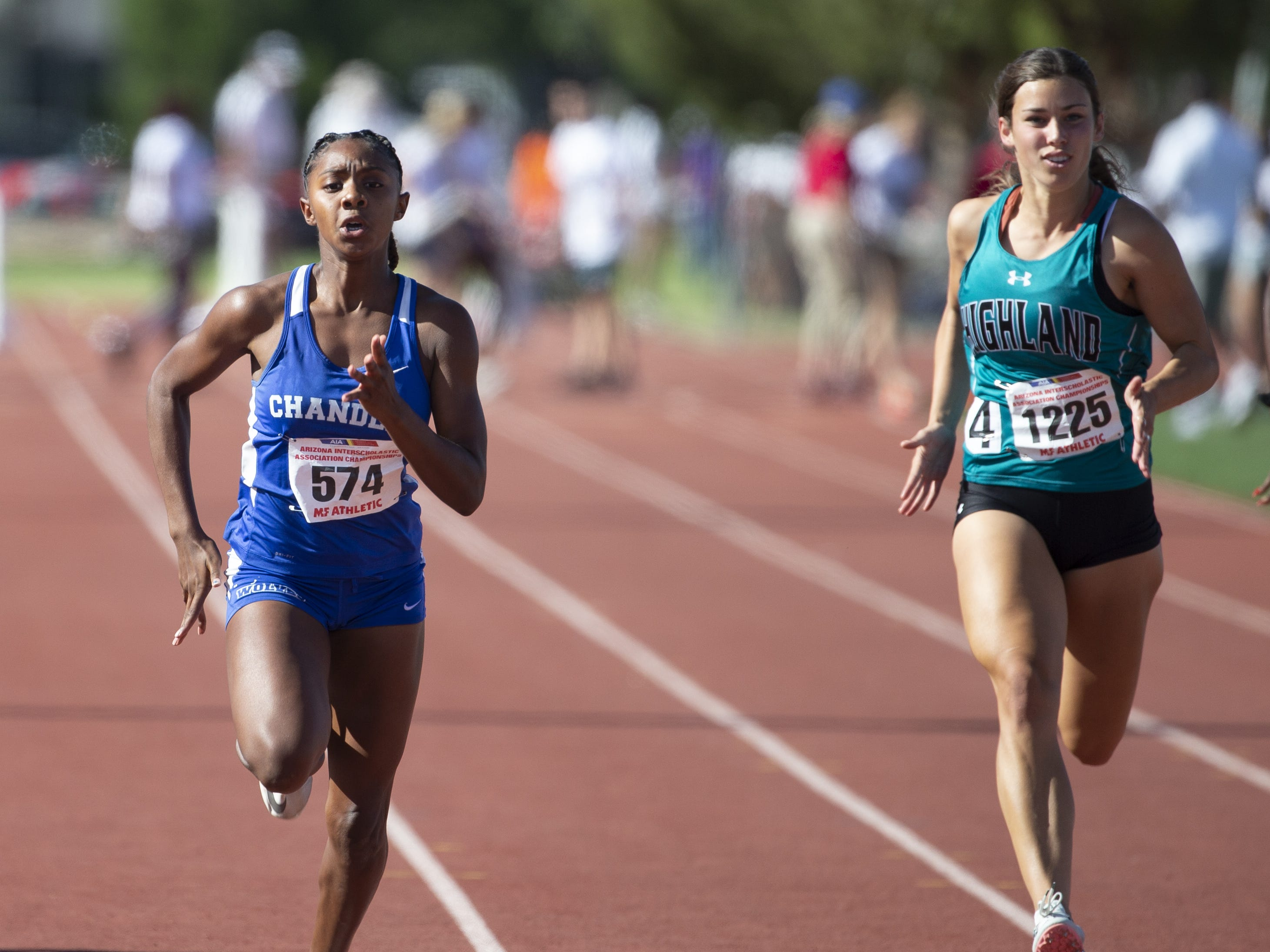 Chandler's Trinity Henderson and Highland's Secret McEuen compete in the Girls 100 meter dash Div. I during the state track and field meet at Mesa Community college on May 1, 2019.