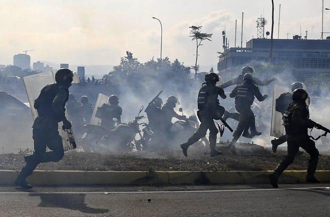 Miembros de la Guardia Nacional Bolivariana leales al presidente venezolano Nicolás Maduro corren bajo una nube de gas lacrimógeno luego de ser rechazados con disparos de rifles por guardias que apoyan al líder opositor venezolano y al autoproclamado presidente interino Juan Guaidó frente a la base militar