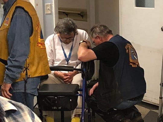 Dave Simmons of North Lebanon kneels and prays with a resident of Lebanon's American House, a personal care facility.