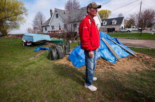 Dennis Sutton stands in his yard near a mound of sand and filled sandbags Thursday, May 2, 2019 in Clay Township. Sutton was hoping to fill 100 sandbags, which he said still wouldn't be enough to stop the river from flooding into his yard.