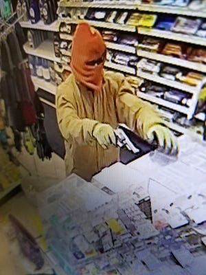 A security photo shows a masked individual attempting to rob a Mobil station in Pleasant Valley on Tuesday night.