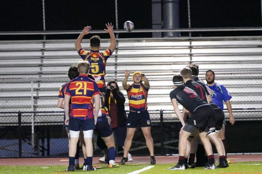 Raymond McGettigan throws the ball during a lineout. McGettigan plays the position of hooker.