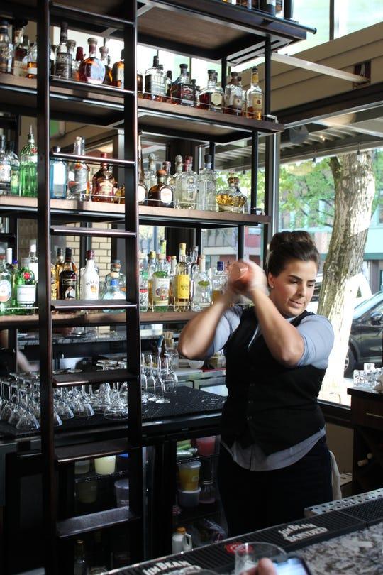 Katelyn Hawley shakes a cocktail behind  the new bar at Ritter's on May 1, 2019.