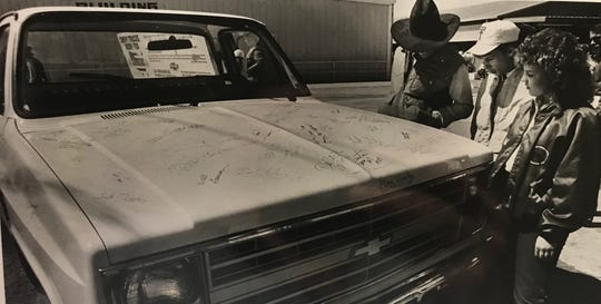 A Chevy truck with the signatures of Farm Aid performers is inspected at the San Angelo Fairgrounds in March of 1987. The truck was given away as part of a fund raiser.