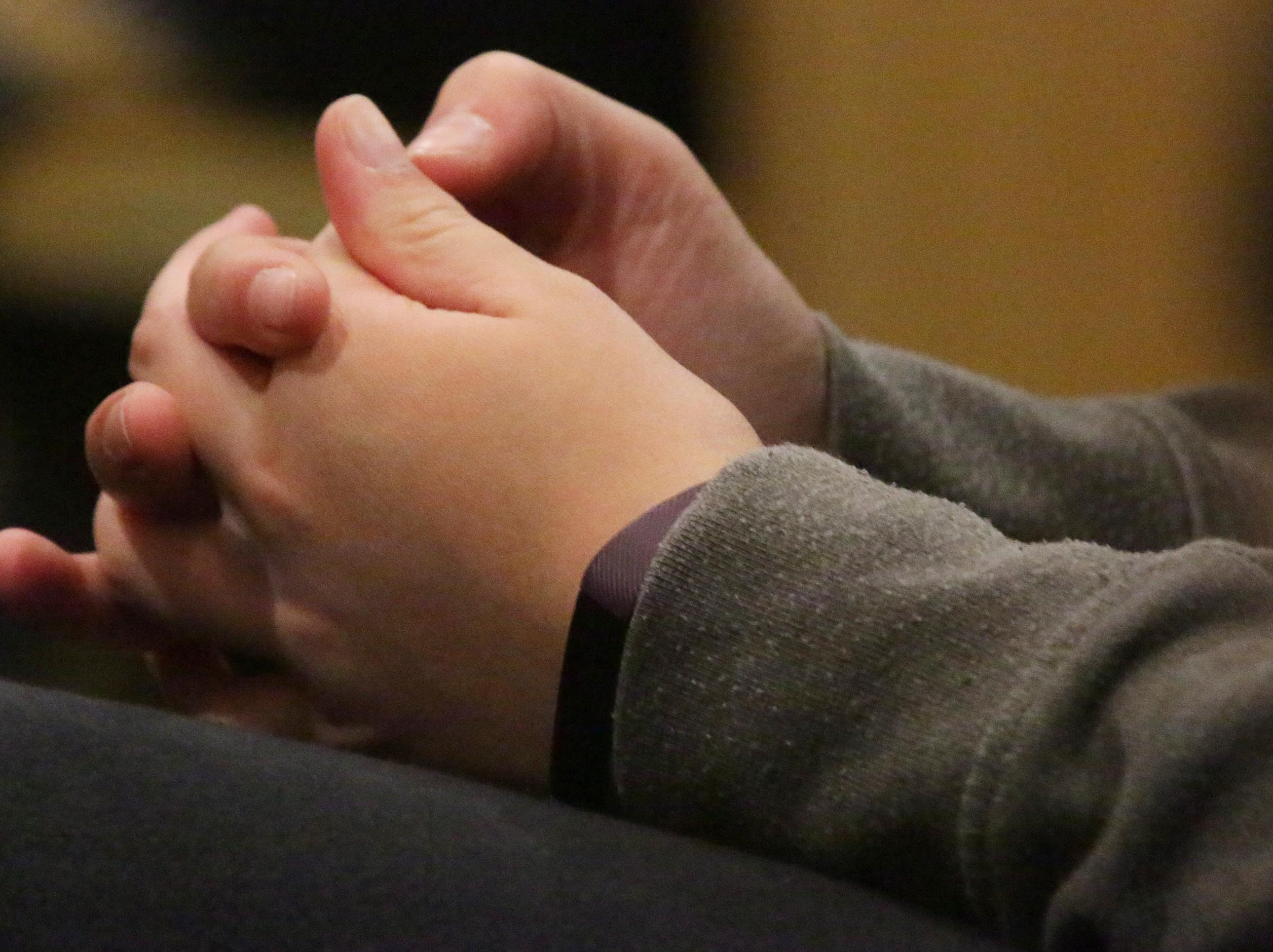 A young person's hands are clasped in prayer during the National Day of Prayer, Thursday, May 2, 2019, at Fountain Park Church, in Sheboygan, Wis.