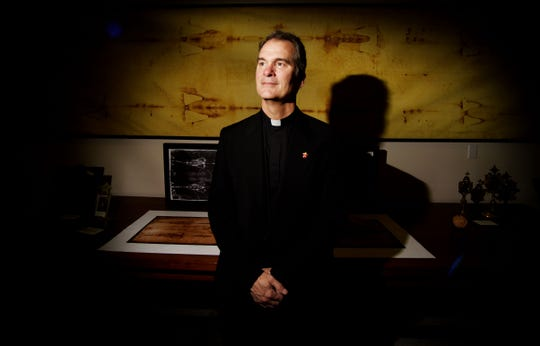Fr. Peter Mangum stands in front of an exact replica of the Holy Shroud that is part of the collection at The Museum of the Holy Shroud at the Cathedral of St. John Berchmans in Shreveport, Louisiana.