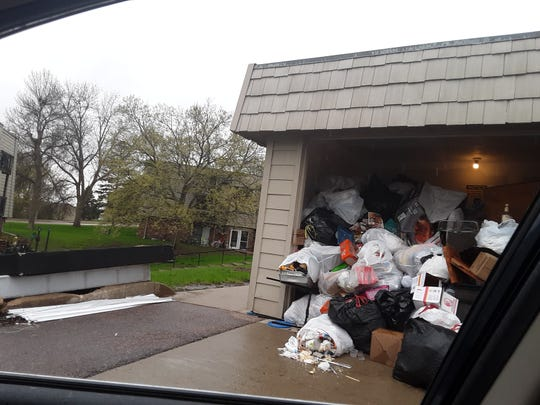 A submitted photo shows garbage piled up in a single-stall garage at Willow Wood apartments in Sioux Falls. The property was purchased by Florida-based Tzadik Management in March.