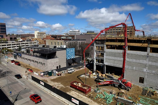 Construction crews work on the new parking ramp at the Village on the River development in downtown Sioux Falls on Thursday, May 2.