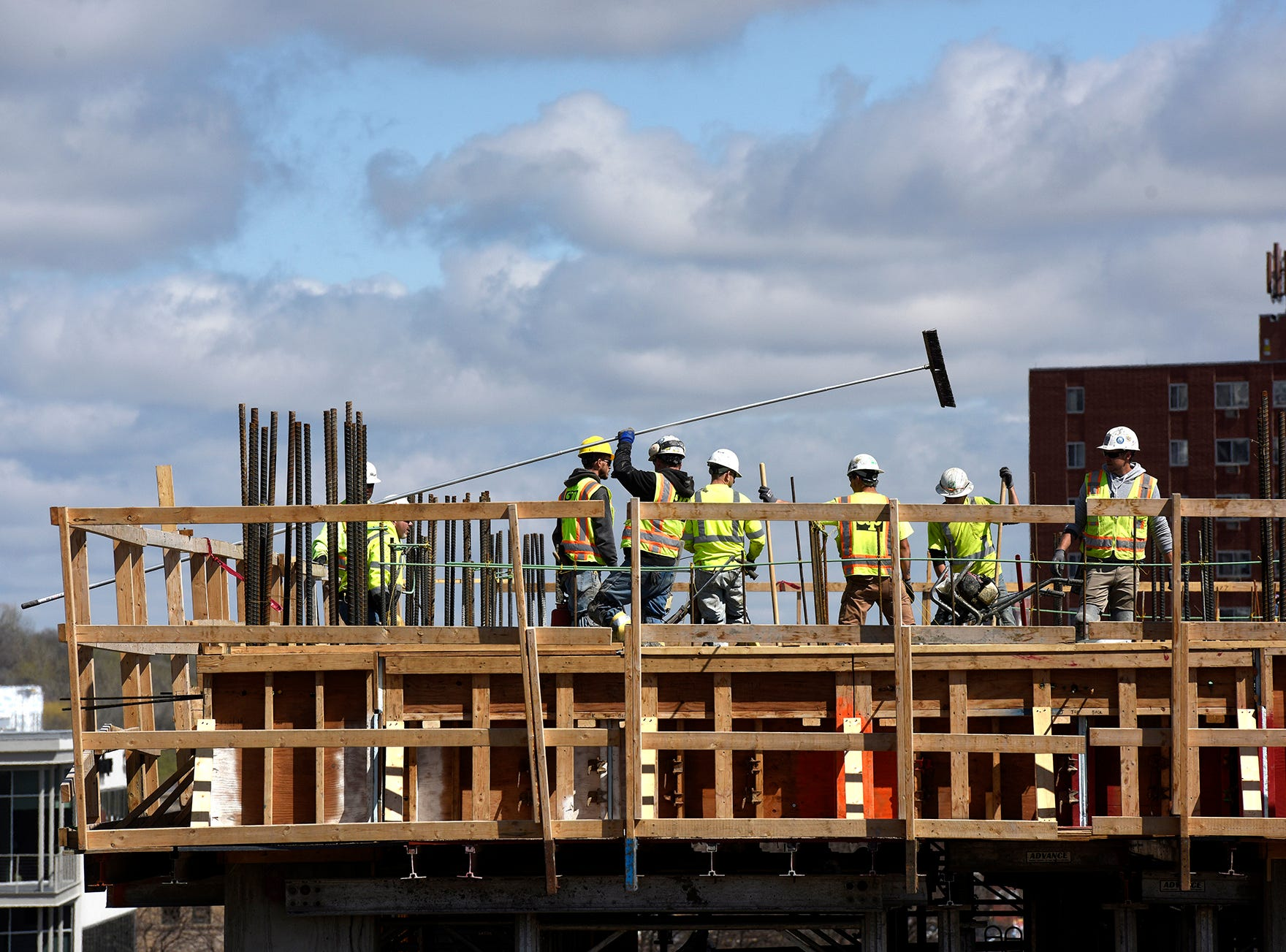 Construction crews work concrete on one of the top levels of the new parking ramp at the Village on the River development in downtown Sioux Falls on Thursday, May 2.