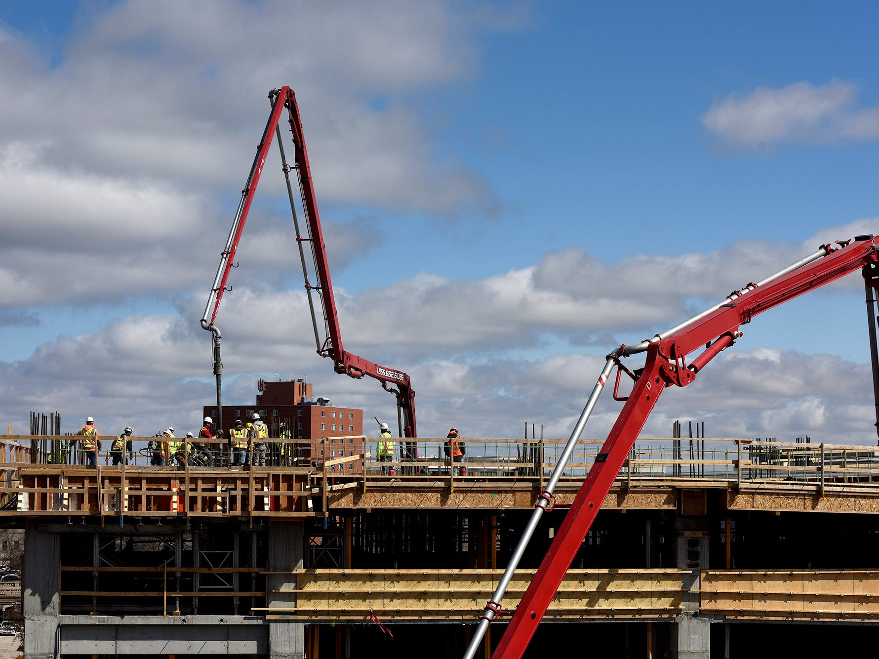Construction crews pour concrete on one of the top levels of the new parking ramp at the Village on the River development in downtown Sioux Falls on Thursday, May 2.