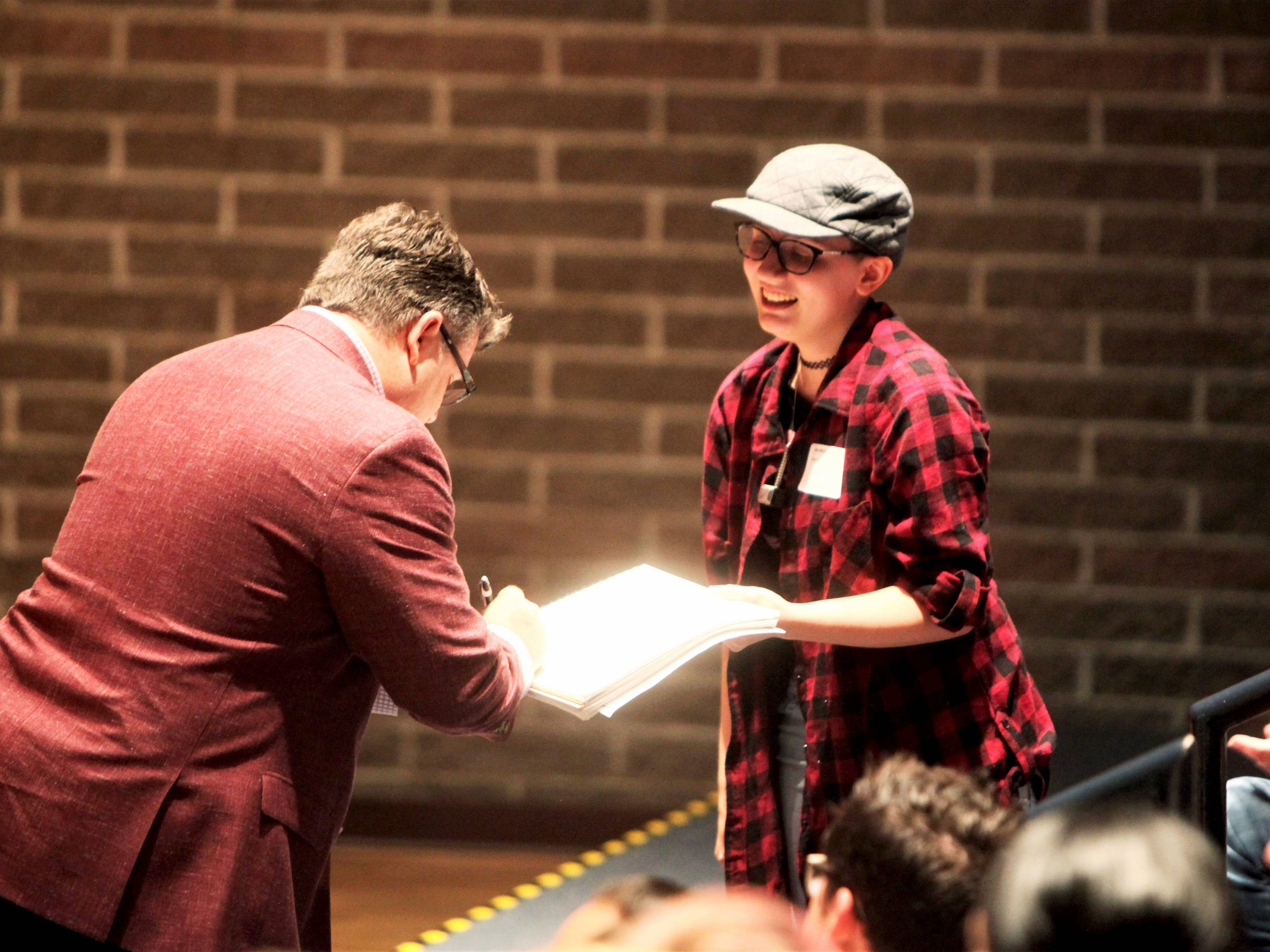 Sean Astin autographs a sketch by Emma McGlumphry, a Missouri State University freshman and animation major, during a keynote speech Wednesday, May 1, 2019.