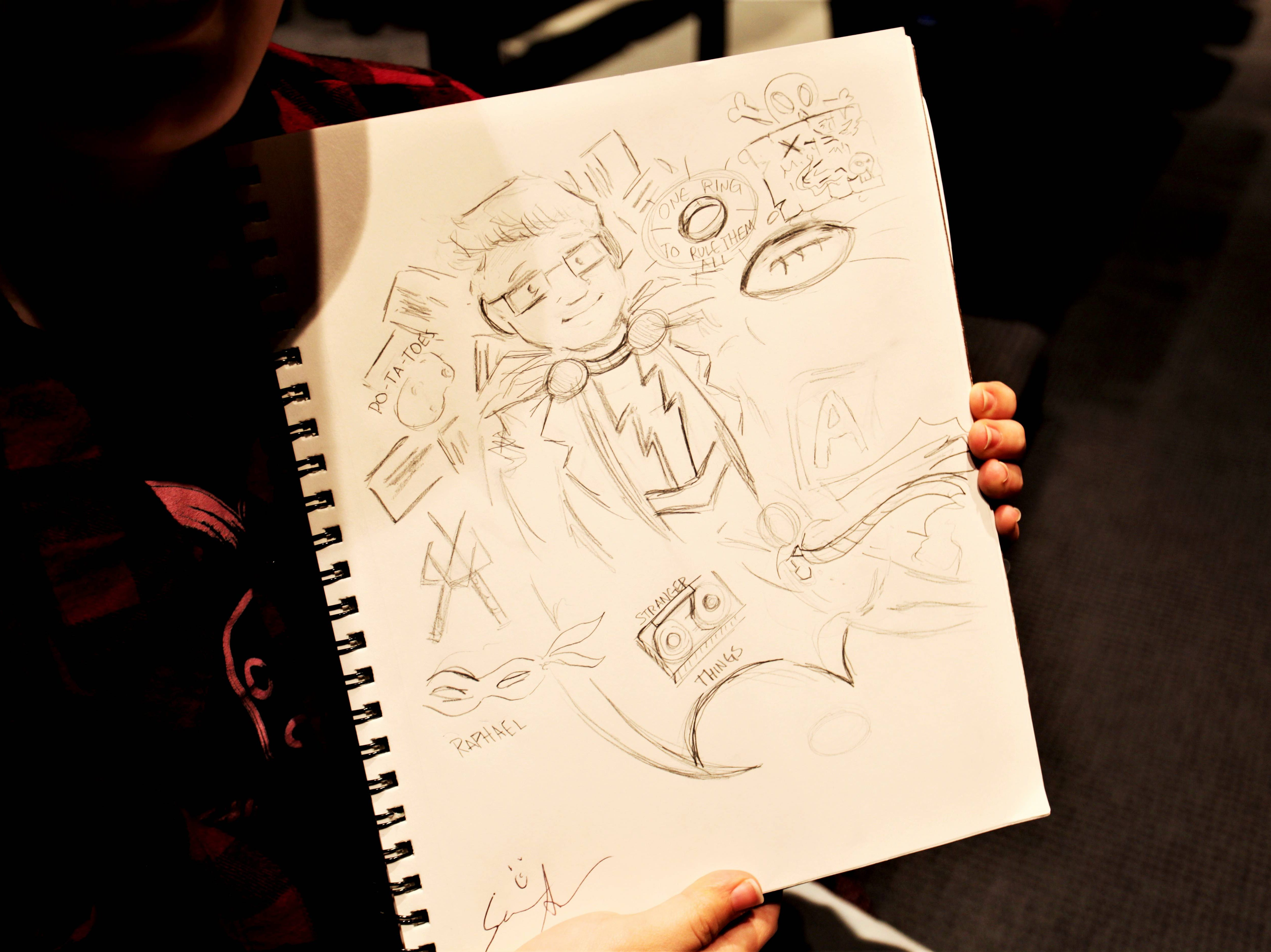 Emma McGlumphry, a Missouri State University freshman and animation major, displays a sketch she drew during a keynote speech by Sean Astin Wednesday, May 1, 2019. Astin autographed the drawing during his speech.