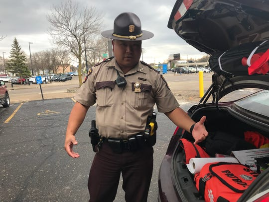 Peter Bachhuber, a Minnesota State trooper, describes the gear troopers carry in their squad cars in St. Cloud on Monday, April 29th.
