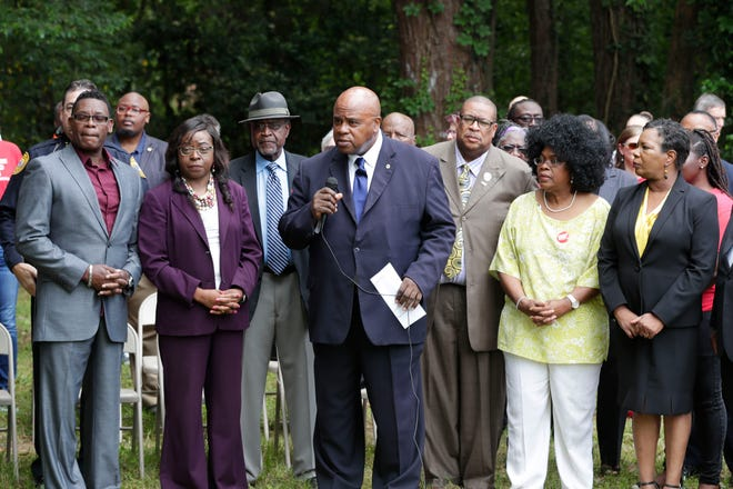 Curtis Taylor, interim president and CEO of the Tallahassee Urban League, center, speaks at a press conference to address recent gun violence in the Bond neighborhood and Tallahassee community Thursday, May 2, 2019.Taylor is surrounded by members of the Bond community as well as local and elected officials.
