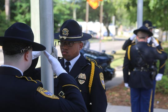 The Tallahassee Police Department's honor guard salutes before drawing flags to half-staff.