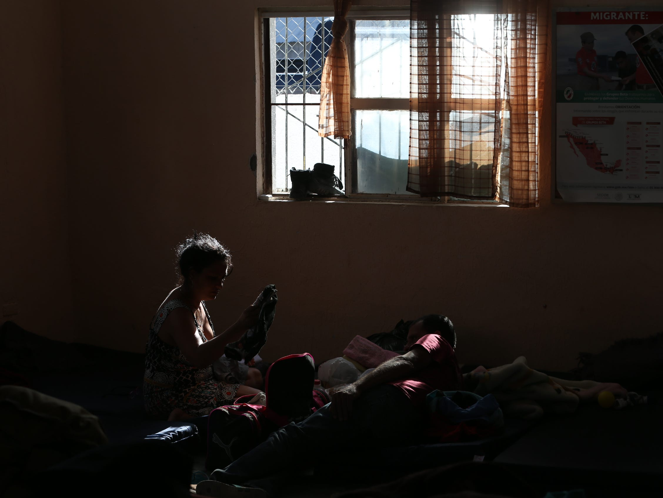 A woman from El Salvador organizes her family's clothing a the Albergue Para Migrantes in Juarez as they await their initial asylum hearing.