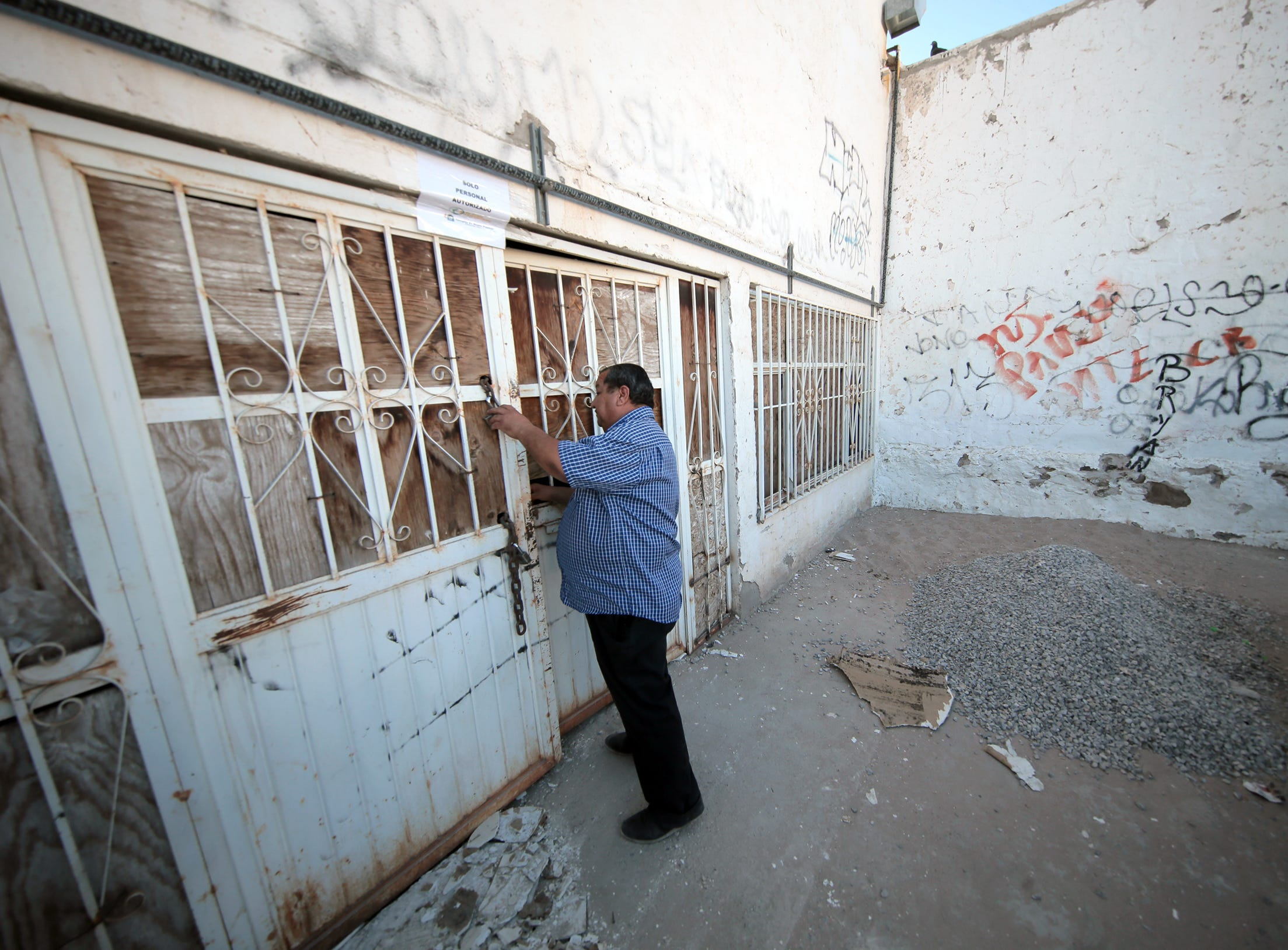 """Pastor Juan Fierro locks up a warehouse he is converting into additional shelter space for asylum seekers in Juarez. His current shelter Albergue Para Migrantes """"El Buen Pastor,"""" which is across the street, is at capacity."""