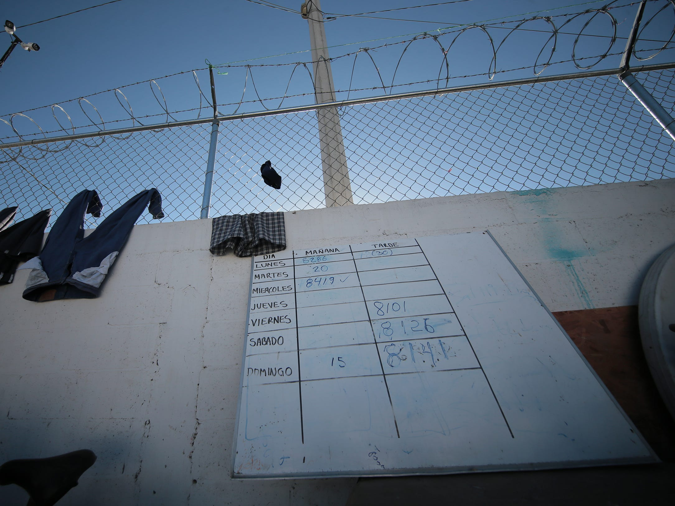 """A tote board in the courtyard of the Albergue Para Migrantes """"El Buen Pastor"""" lets asylum seekers know when their number is close. Many at the shelter had numbers well over 12,000."""