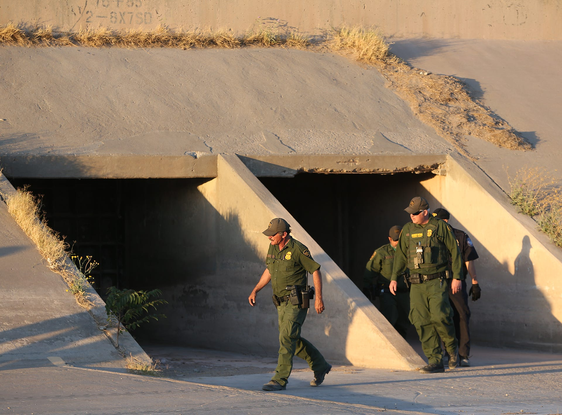 Border Patrol agents check a tunnel in the Rio Grande basin Wednesday as they search for asylum seekers Wednesday between El Paso and Juarez.