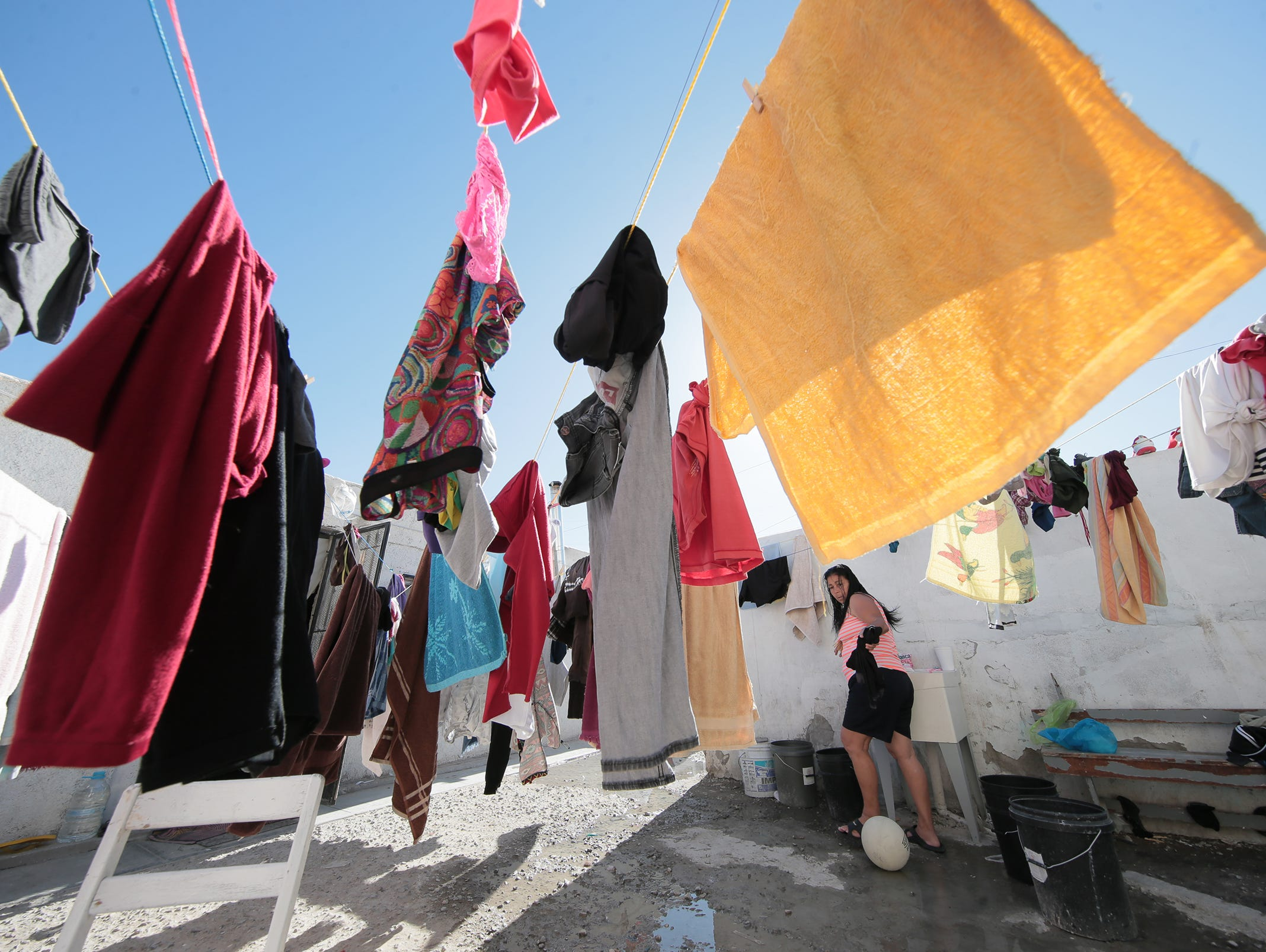 """A Central American asylum seeker washes her family's laundry in a sink at the Albergue Para Migrantes """"El Buen Pastor"""" in Juarez. Asylum seekers are seeing long waits for their number to be called by U.S. authorities."""