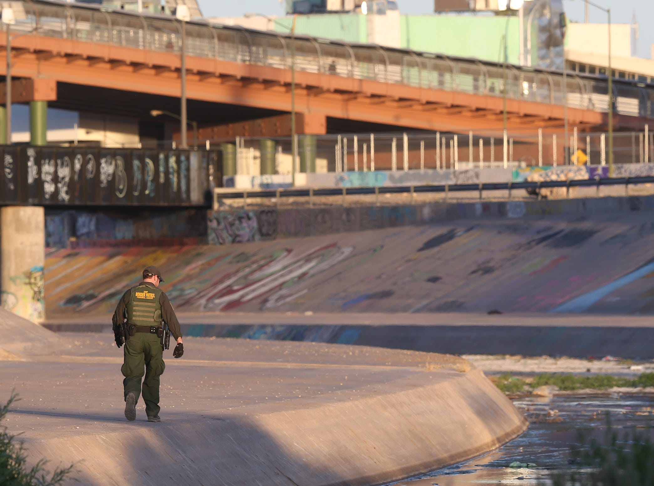 A Border Patrol agent walks the levee near the Paso del Norte International Bridge in El Paso Wednesday.