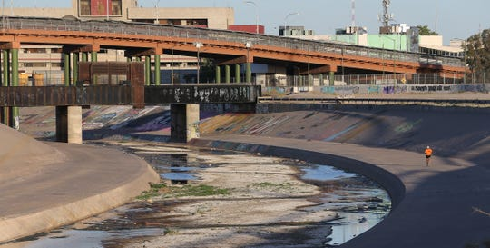 A runner makes his way along the Rio Grande between Juarez and El Paso Wednesday near the Paso del Norte International Bridge.