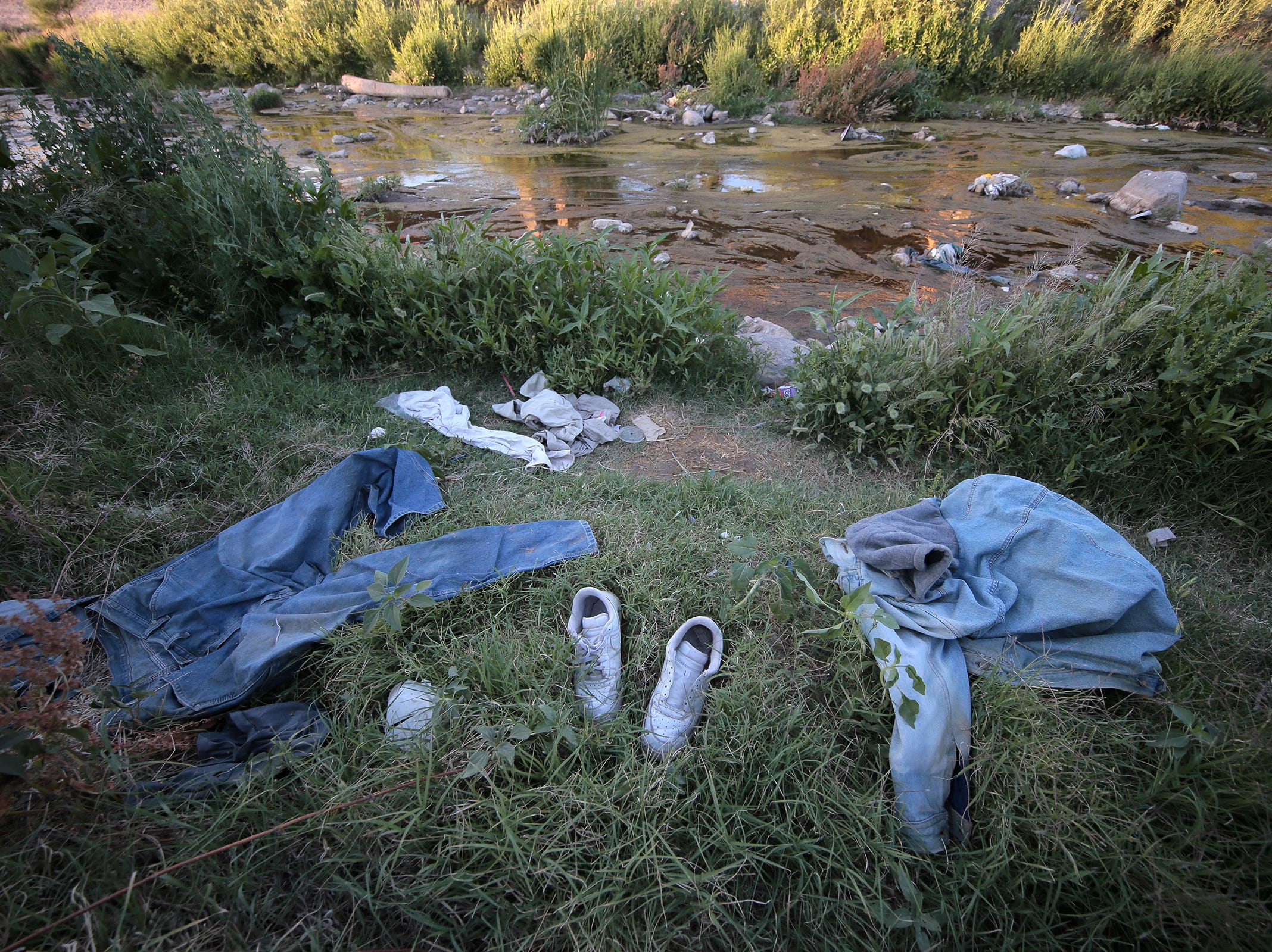 Clothing left behind by migrants litter the banks of the Rio Grande between El Paso and Juarez.