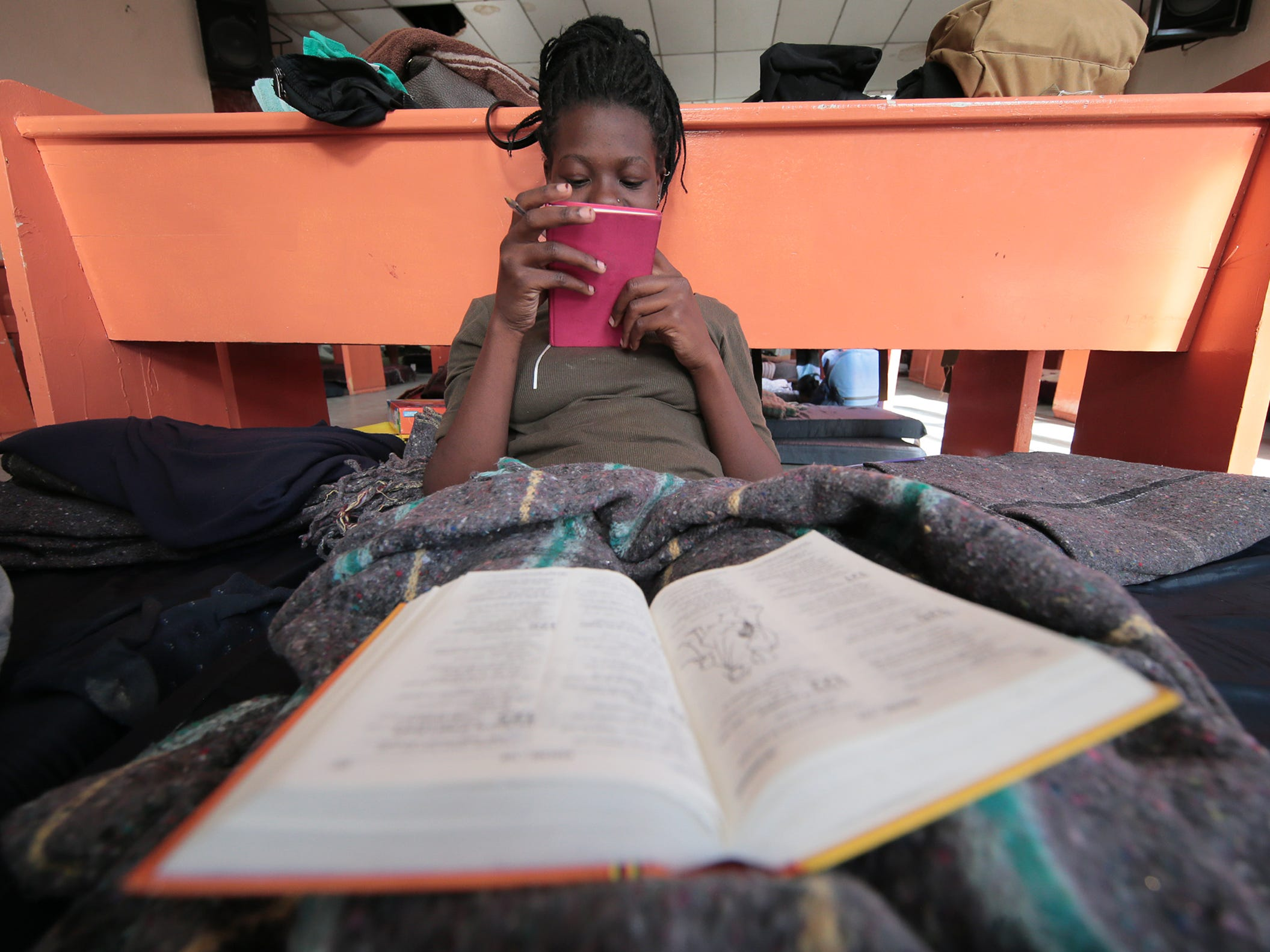 """A Ugandan asylum seeker studies her bible as she waits for her number to be called by U.S. authorities to plead her asylum case. A group of Ugandans are at the Albergue para Migrantes """"El Buen Pastor"""" in Juarez."""