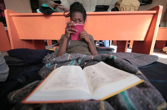 "A Ugandan asylum seeker studies her bible as she waits for her number to be called by U.S. authorities to plead her asylum case. A group of Ugandans are at the Albergue para Migrantes ""El Buen Pastor"" in Juarez."