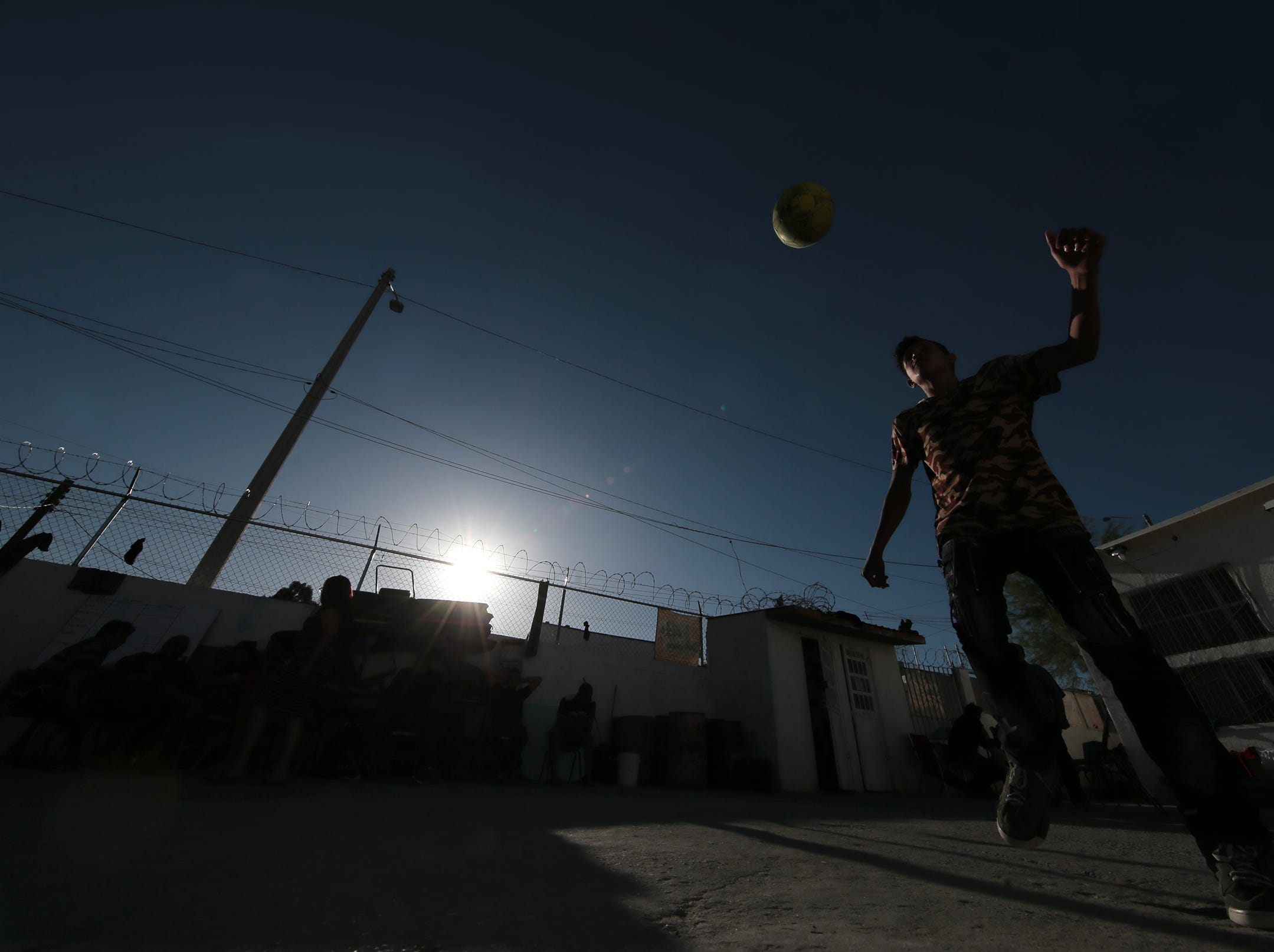 """A teen asylum seeker plays soccer in the courtyard of the Albergue Para Migrantes """"El Buen Pastor"""" in Juarez. The migrants are awaiting their number to be called by U.S. authorities for their intitial hearing."""