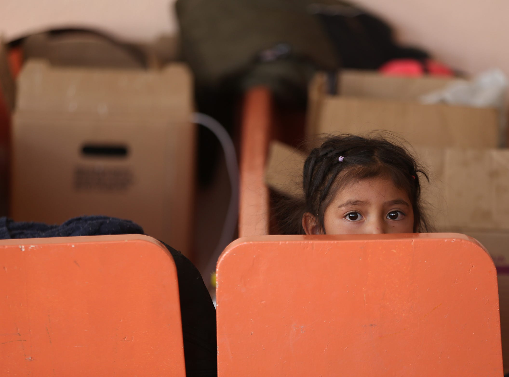"""A Guatemalan girl peeks from behind the pew she sleeps in at the Albergue Para Migrantes """"El Buen Pastor"""" as her family awaits their number to be called for their initial asylum hearing."""