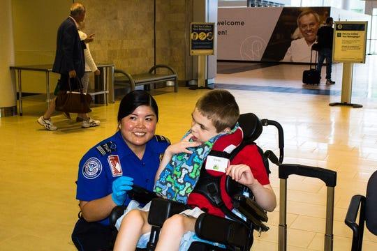A TSA agent assists a special needs child.