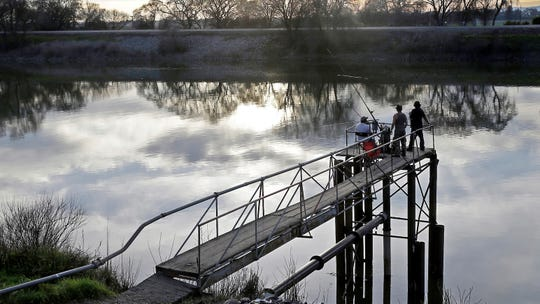 In this 2016 file photo, people try to catch fish along the Sacramento River in the San Joaquin-Sacramento River Delta, near Courtland, California