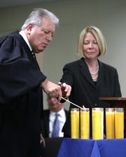 Judges Robert Berliner and Linda Christopher light a candle at the Yom HaShoah commemoration at the Rockland County courthouse May 2, 2019.