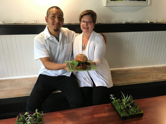 "Chef Carlos Martinez and Dexter's Den proprietress, Emily Feliciano hold ""The Full Dexter,"" made with organic, humanely raised beef, Vermont bacon, Imported Gruyere and house brewed BBQ sauce."