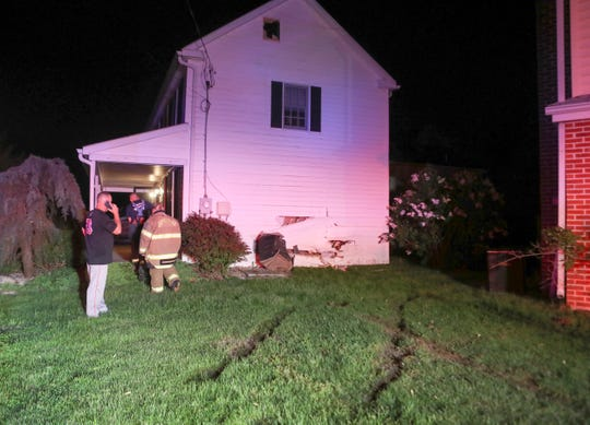Firefighters investigate after a hit-and-run driver smashed into the side of a house on the 1700 block of Bear Corbitt Road in Bear shortly before 9 p.m. Wednesday.