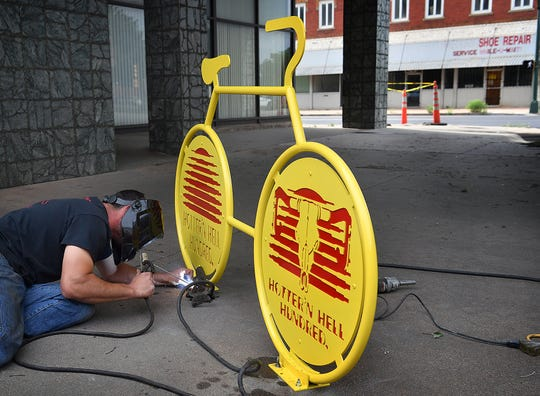 T.J. Johnson of TJWeldIt installs the seventh sculptural bike rack in downtown Wichita Falls Thursday afternoon. The rack is located in the 700 block of Scott Avenue.