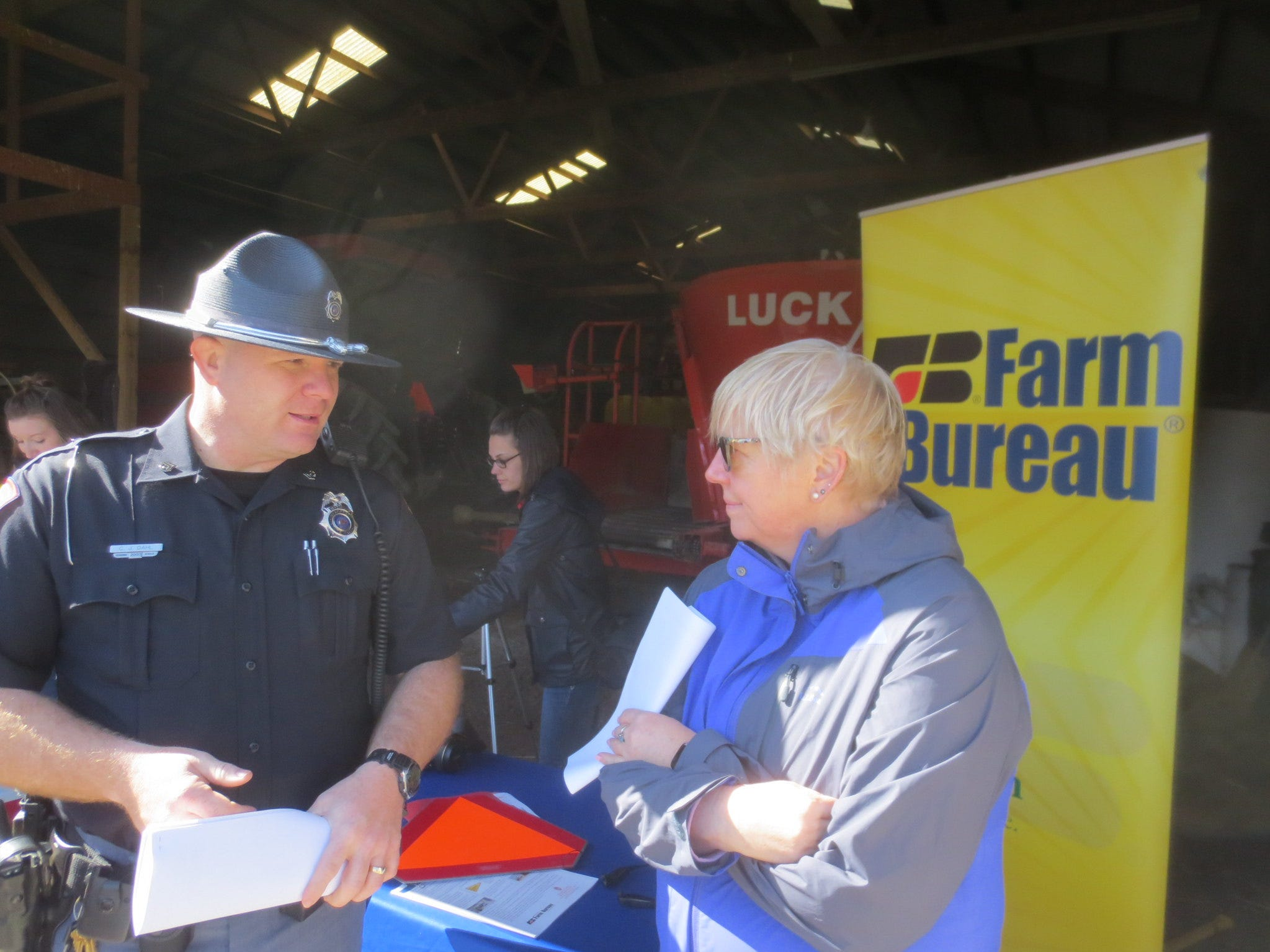 Safety Patrol officer CJ Dahl compares notes with Cheryl Skjolaas,  Agricultural Safety and Health Specialist for UW Extension, during the Rural Road Safety Media Day held April 26 at Larrand Dairy near DePere, Wis.