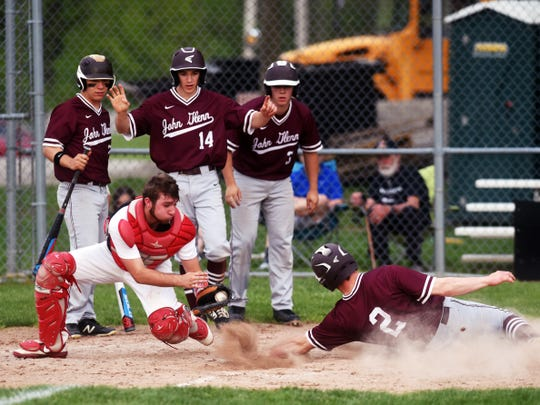 Ben Larson slides into home while being tagged by Kadin Mount during John Glenn's 13-3 win against Crooksville,  John Glenn's Score Perkins, Blade Barclay and J.D. Brown watch the play behind the plate.