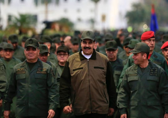 In this handout photo released by Miraflores Press Office, Venezuela's President Nicolas Maduro, center, accompanied by Defense Minister Gen. Vladimir Padrino Lopez, left, and the Strategies Operations Commander, Adm. Remigio Ceballos, arrive for a meeting with the troops at Fort Tiuna in Caracas, Venezuela, Thursday, May 2, 2019.