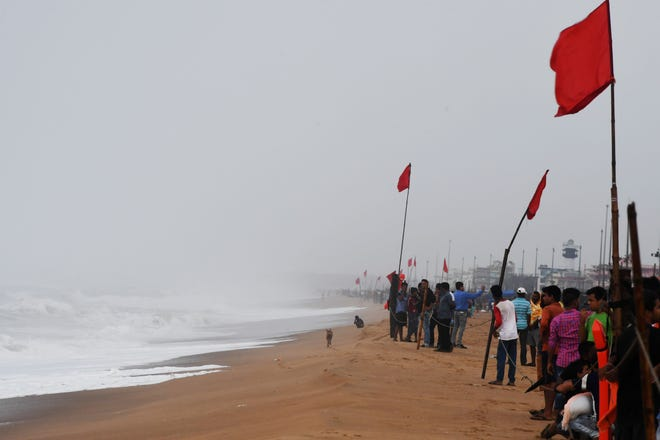People look out towards the sea from a closed beach in Puri in the eastern Indian state of Odisha on May 2, 2019, as Cyclone Fani approached the Indian coastline.