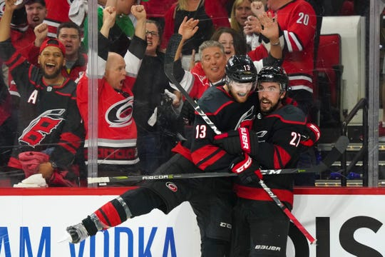 Carolina Hurricanes defenseman Justin Faulk (27) celebrates with forward Warren Foegele (13) after scoring a goal in the second period against the New York Islanders.