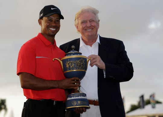 Tiger Woods stands with Donald Trump as he holds the Gene Serazen Cup for winning the Cadillac Championship golf tournament March 10, 2013, in Doral, Florida.