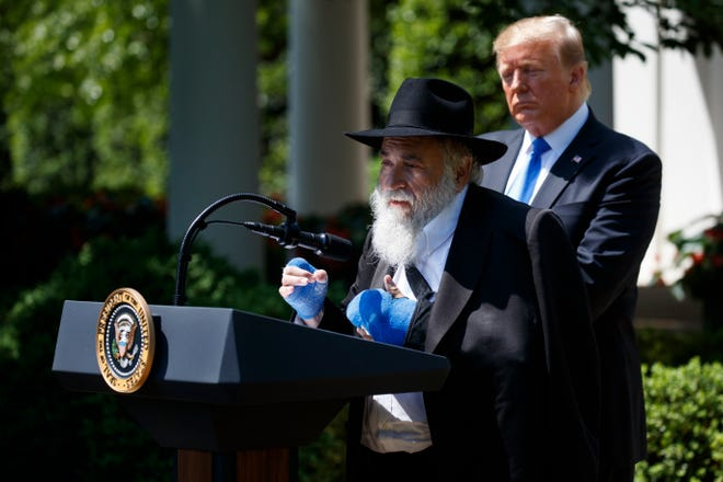 President Donald Trump looks on as Rabbi Yisroel Goldstein, a survivor of the Poway, Calif., synagogue shooting, speaks during a National Day of Prayer event in the Rose Garden of the White House in May 2019.