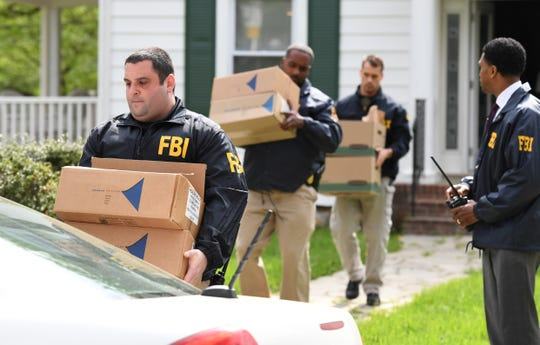 Federal agents remove items from the home of Baltimore Mayor Catherine Pugh as they execute a search warrant.