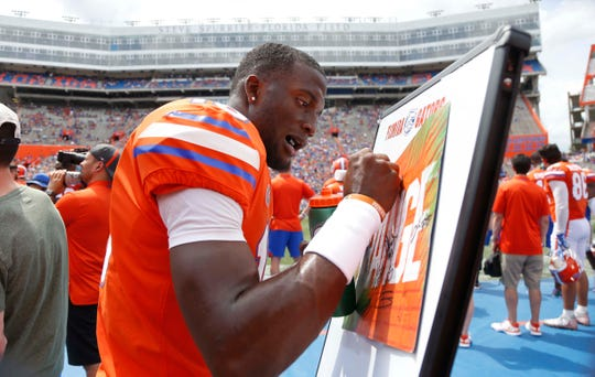 Former Florida Gators quarterback Jalon Jones (18) sign an autograph during the second half at Ben Hill Griffin Stadium at Florida Field.